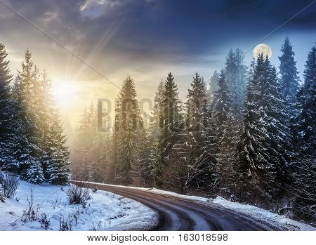 day and night concept of winter forest landscape. winding road that leads into the spruce forest covered with snow