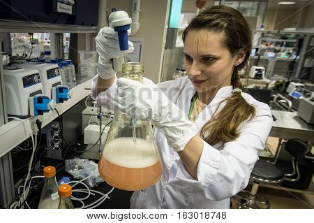 Woman Laboratory Assistant With Flask In His Hand In The Biochemical Laboratory