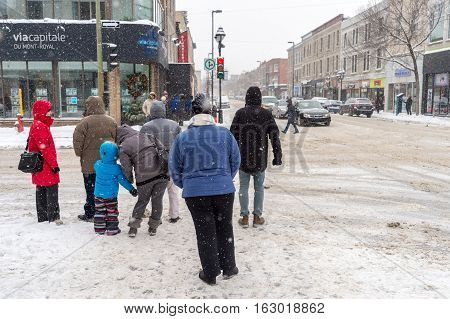 Montreal CA - 17 December 2016: Snowstorm in Montreal. Pedestrians on Mont-Royal Avenue.