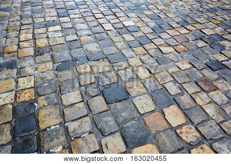 Wet cobbles. Paving stone. Texture background. Old cobblestone on the streets.