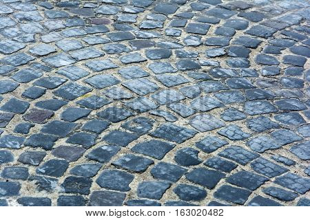 Paving stone. Texture, background. Old cobblestone on the streets.