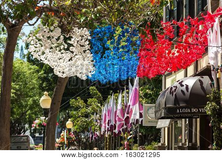 FUNCHAL MADEIRA PORTUGAL - SEPTEMBER 1 2016: Colorful decorations from garlands over streets during the Madeira Wine Festival in Funchal on Madeira Island. Portugal