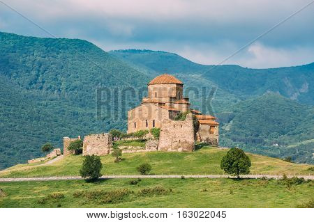 Mtskheta, Georgia. The Scenic View Of Jvari, Georgian Orthodox Monastery, World Heritage By UNESCO. High Mountains Hills Covered With Green Vegetation Background.
