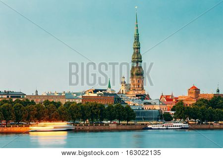 Riga, Latvia. The View Of Daugava River Embankment, Old Town And The Tower With Green Steeple Of St. Peter's Church In Summer Dusk Under Blue Sky. Motion Blurred Abstract Effect On Water Surface.