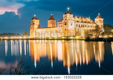 Mir, Belarus. Picturesque View Of Mir Castle Complex In Bright Evening Illumination With Glow Reflexions On Lake Water. Famous Landmark, Ancient Gothic Monument Of Feudalism Under Blue Dramatic Sky.
