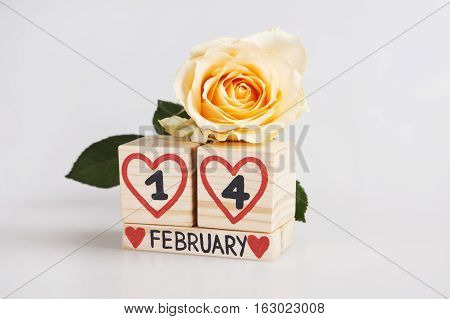 Valentine's day composition with wooden calendar and yellow rose. Handwritten February 14th inside red hearts. Bright background.