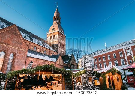 Riga Latvia - December 1 2016: Christmas Market On The Dome Square With Riga Dome Cathedral In Riga Latvia. Trading Houses With Sale Of Christmas Gifts Sweets And Mulled Wine. Famous Landmark.