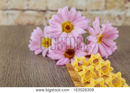 jewish food Jewish Holiday symbol pasta for broth buckwheat a pasta on a background of pink flowers