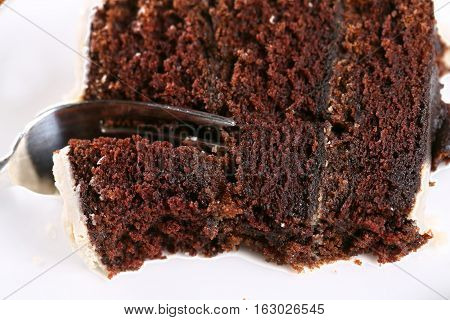 A slice of rich moist chocolate cake on a white plate with layers