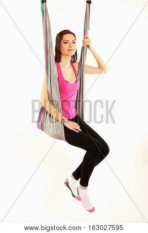 Young woman upside down doing anti-gravity aerial yoga on white background