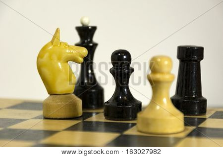 wooden chess pieces black and white pawn officer knight Queen and Bishop on a chess Board table intellectual game
