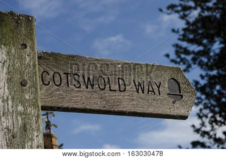 Wooden signpost pointing the direction of the Cotswold Way footpath