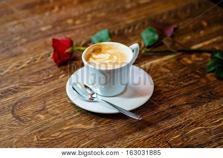 The Cappuccino Cup Is On The Table. Nearby Is The Rose.