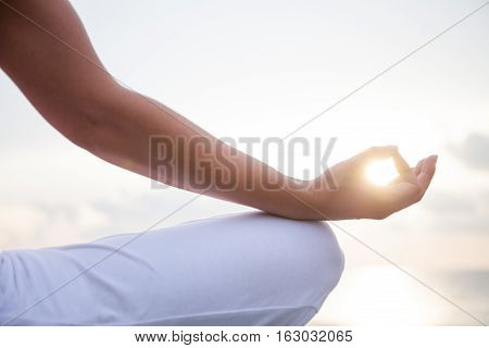 Woman meditating in a yoga pose on the beach on sunset