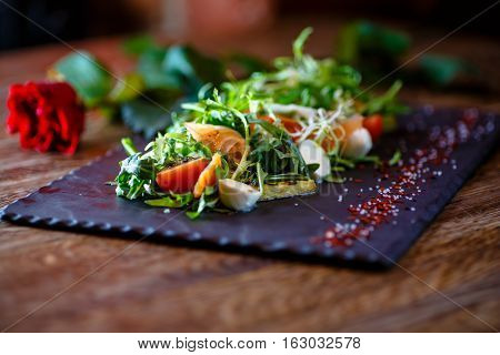 Salad With Salted Salmon With Arugula And Mozzarella On A Black Piece Of Slate.