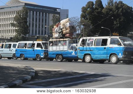 Loaded trucks and blue and white taxis on streets of Addis Ababa, Ethiopia, february 2015