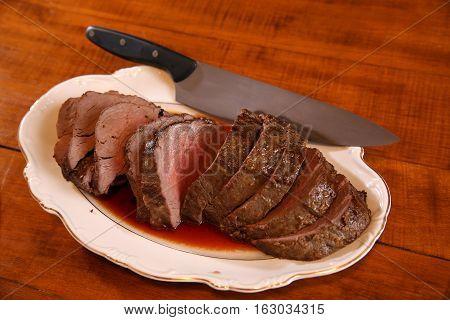 Medium rare beef tenderloin on a platter waiting to be served