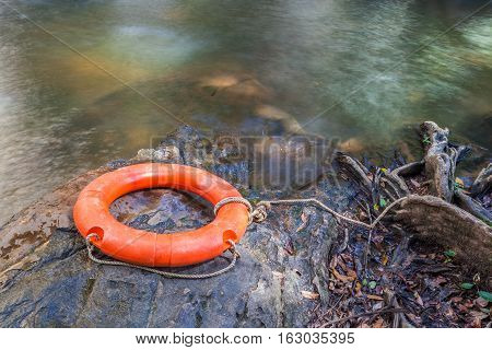 Orange life buoy over the clear water of natural stream rescue concept.