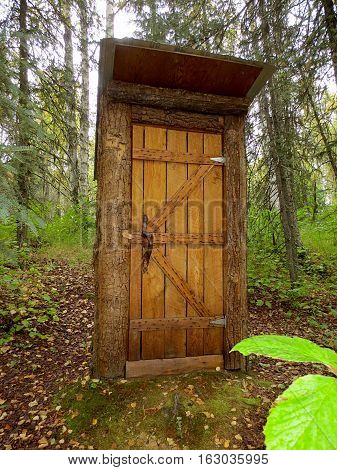 a rustic outhouse set in the woods