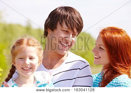Family with a little girl in middle of field in countryside