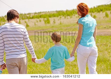 Family with son enjoing a walk in summer nature, view from the back