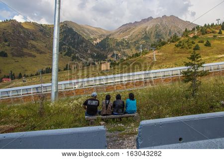 Almaty, Kazakhstan - August 29, 2016: People Sit On The Bench And Looking At The Mountains Near Shym