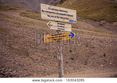 Almaty, Kazakhstan - August 29, 2016: Signpost With Three Arrows With Information On Wooden Road Dir