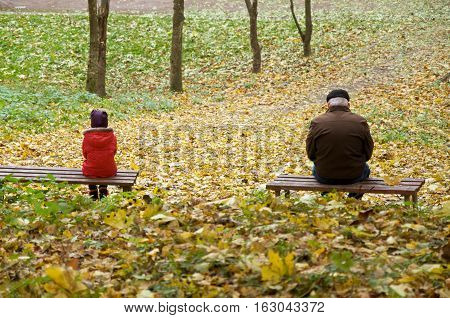 autumn. little girl and an old man quarreled and sit on a bench in the park