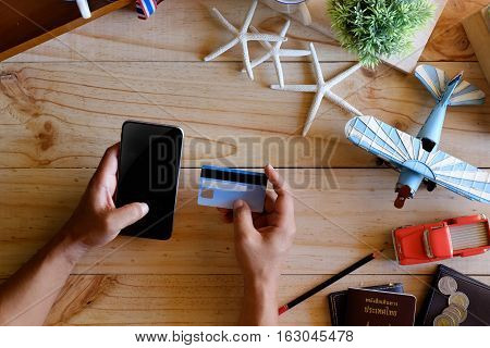 Man booking tickets online by smartphone and credit card. or do online checkin.