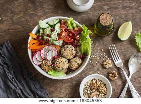 Baked quinoa meatballs and vegetable salad on a wooden table top view. Buddha bowl. Healthy diet vegetarian food concept. Flat lay