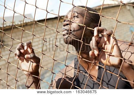 Young African American man behind the fence