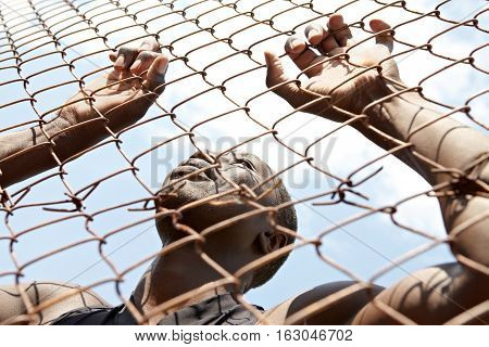 Below view of African American behind the fence in the street