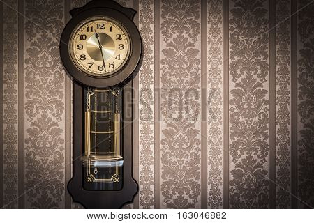 Antique wall clock with a pendulum closeup.