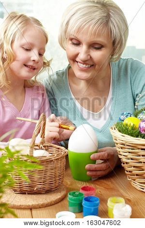 Grandma and her little granddaughter painting a big egg for Easter
