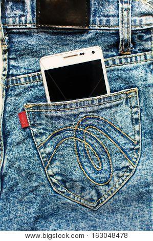 white phone in jeans pocket closeup concapt.