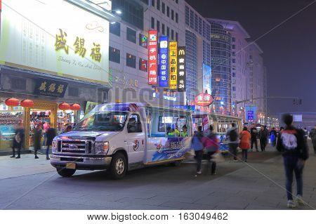 BEIJING CHINA - OCTOBER 24, 2016: Unidentified people ride tourist shuttle bus in Wangfujing shopping street.