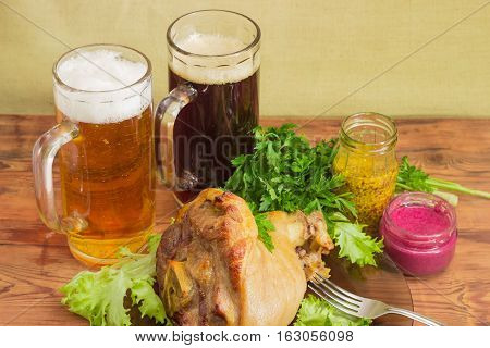 Baked ham hock with lettuce and parsley on a glass dish two glasses of lager beer and dark beer beet horseradish sauce French mustard fork on an old wooden surface