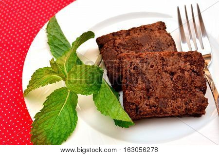 Delicious and soft fresh homemade brownie chocolate square and sliced decorate with peppermint on white dish