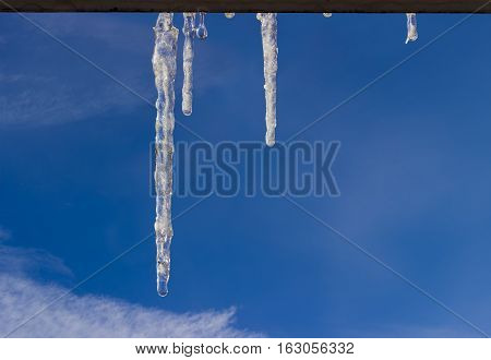 Several icicles with water drops on cornice of window on background of the sky with cirrus clouds