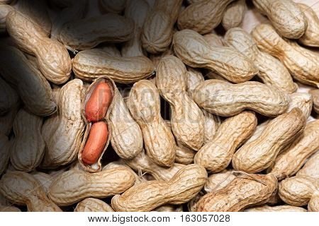 Background with many peanuts in shell with one shelled (open) with dark shadows