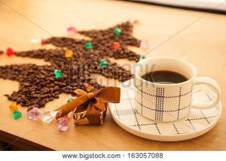 Christmas tree made from coffee beans with decoration and cup of black coffee. Happy new year congratulation with cup of espresso and gift.