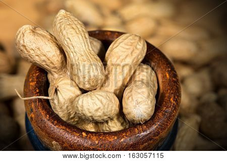 Group of peanuts in shell. In a wooden bowl with dark shadows - Macro photography