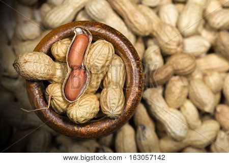 Group of peanuts in shell with one shelled (open). In a wooden bowl with dark shadows - Macro photography