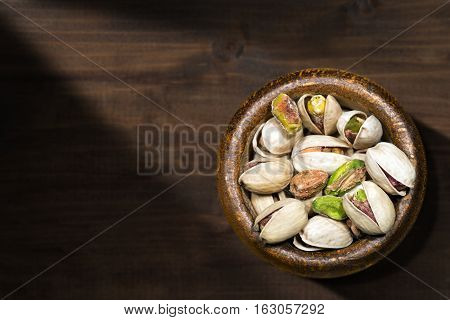 Roasted and salted pistachios in a wooden bowl on a brown table with dark shadows - Macro photography