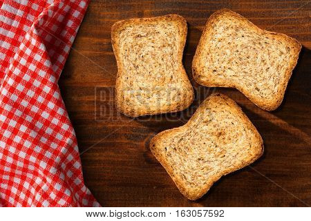 Three healthy rusks of wholemeal flour on a wooden table with red and white checkered tablecloth