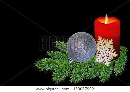 Cristmas toy and burning candle  on black background