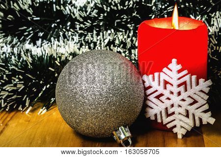 Cristmas toy and burning candle  on background of pine-needles