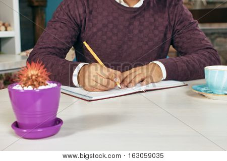 Young man holding a pencil, writing on a paper in the diary
