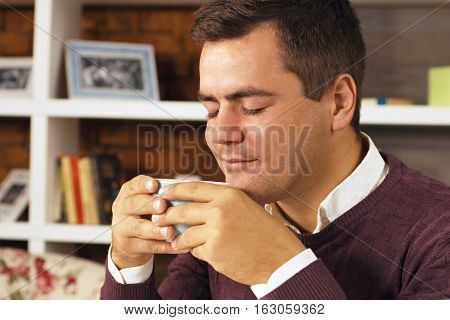 Young man enjoying with closed eyes drink coffee, tea or chocolate.