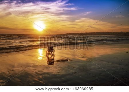 Sunset on the beach handicapped wheelchair. Background